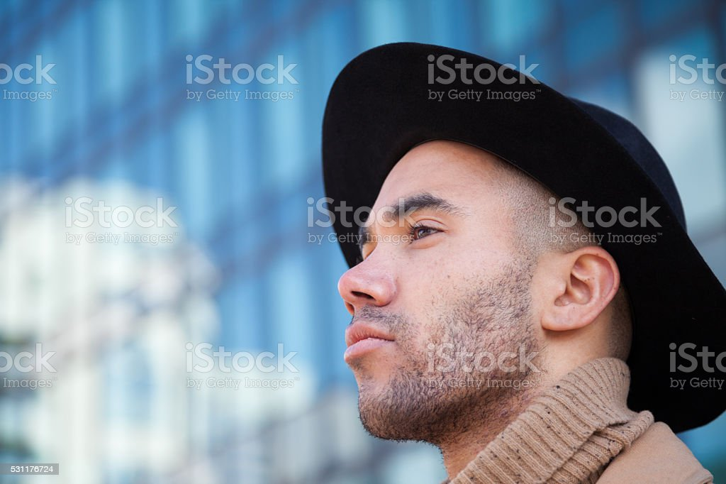 confident fashionable young businessman in trilby by skysscraper reflecting clouds stock photo