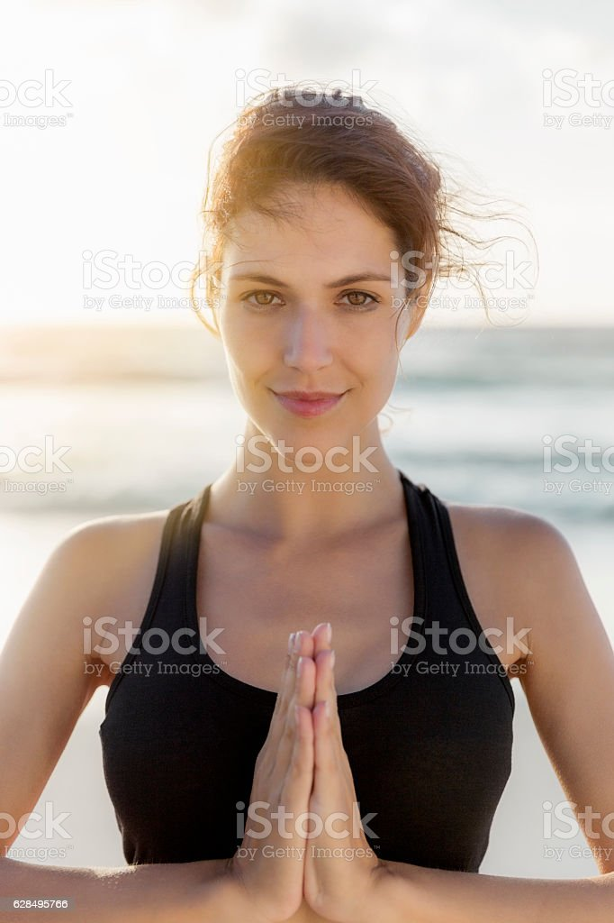 Confident female athlete doing yoga at beach stock photo