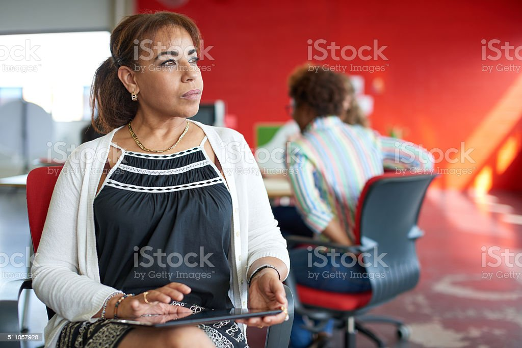 Confident female boss working on a digital tablet in red stock photo