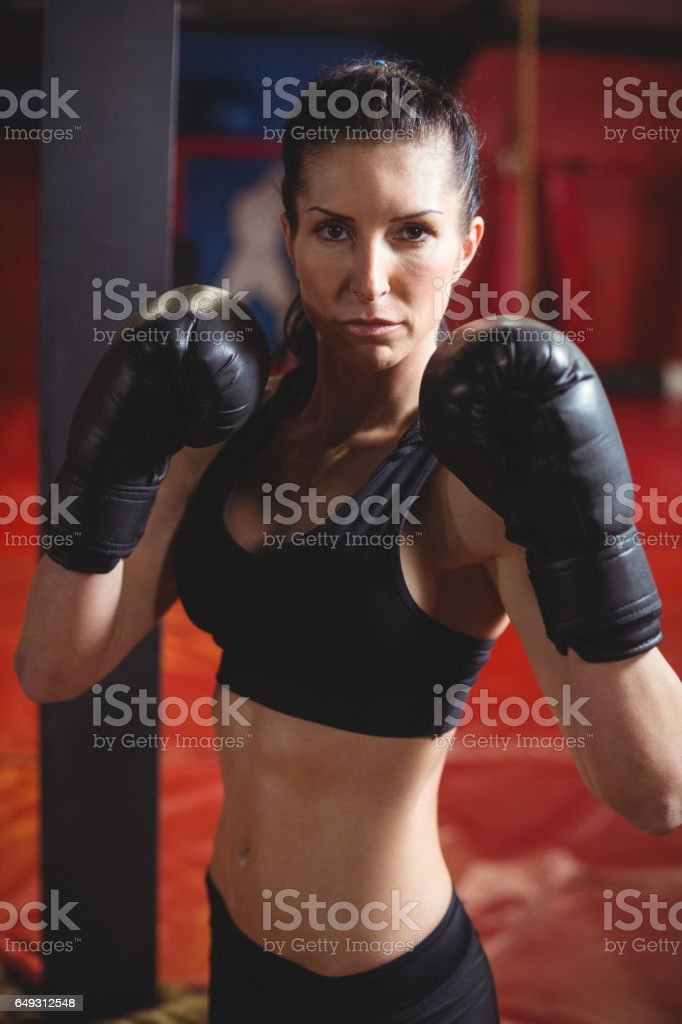 Confident female boxer performing boxing stance stock photo