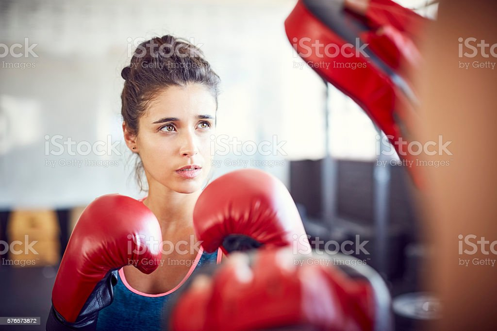 Confident female boxer practicing in health club stock photo