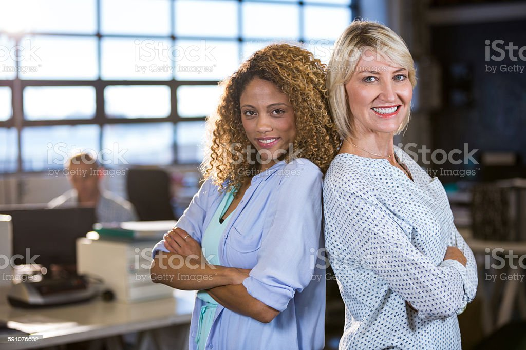 Confident female colleagues standing back to back stock photo