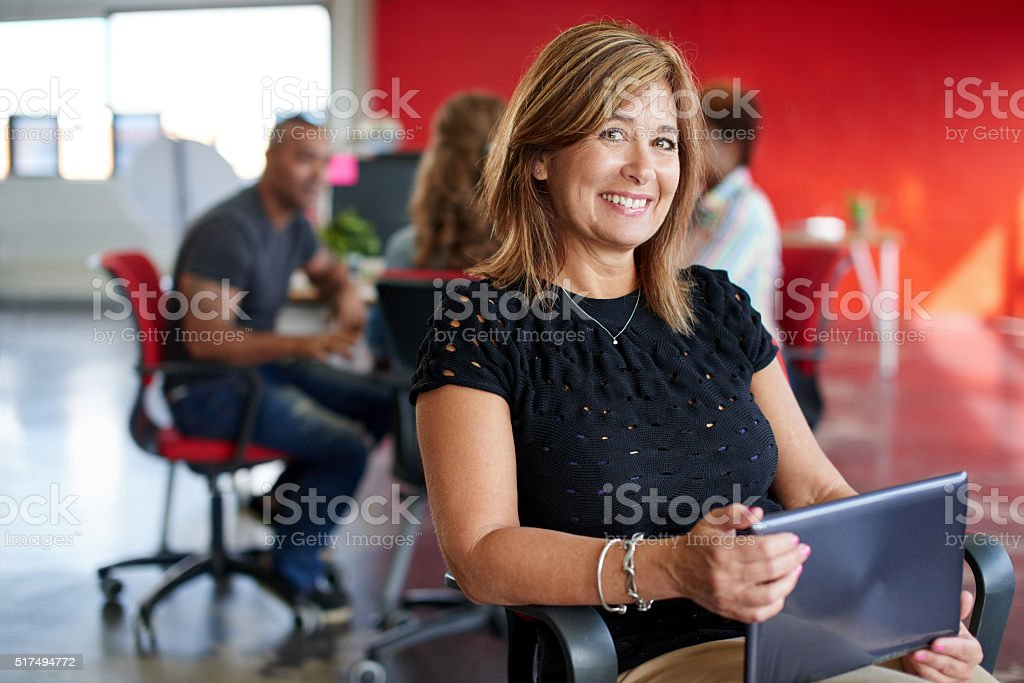 Confident female designer working on a digital tablet in red stock photo