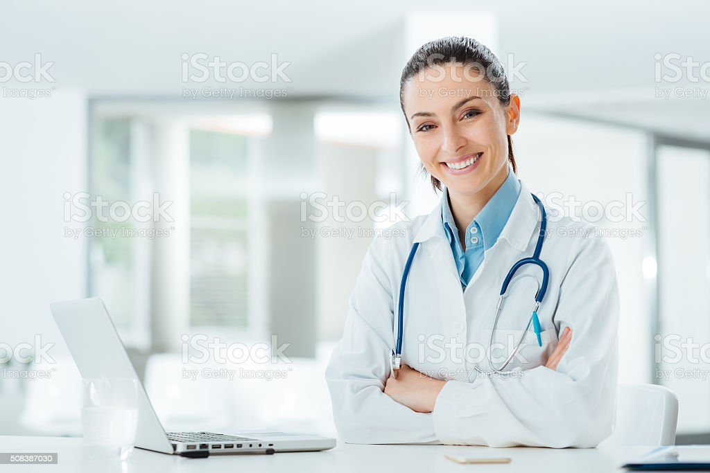 Confident female doctor at office desk stock photo