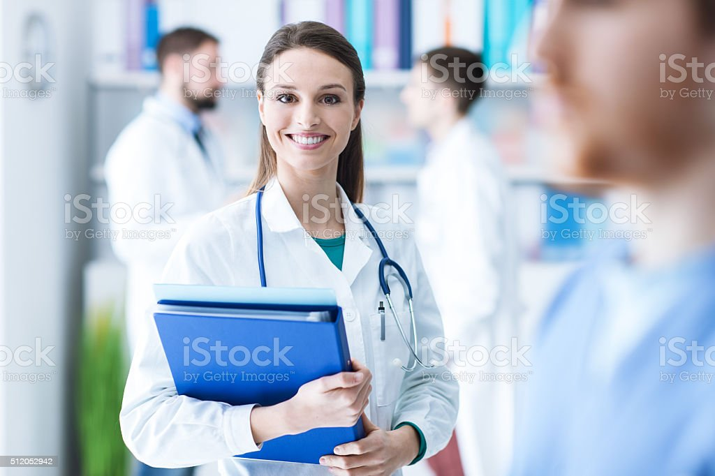 Confident female doctor holding medical records stock photo