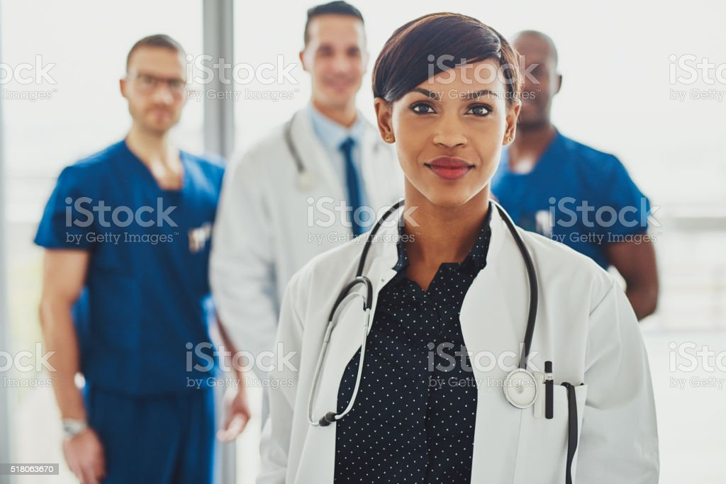 Confident female doctor in front of team stock photo