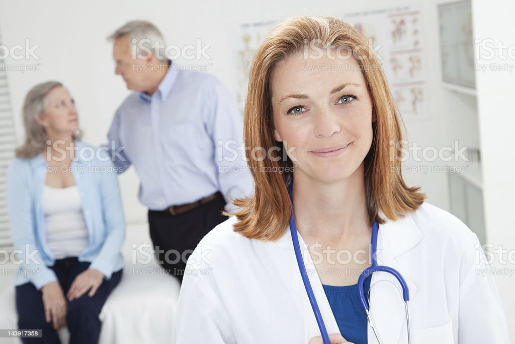 Confident Female Doctor in Office with Senior Adult Patient Couple royalty-free stock photo