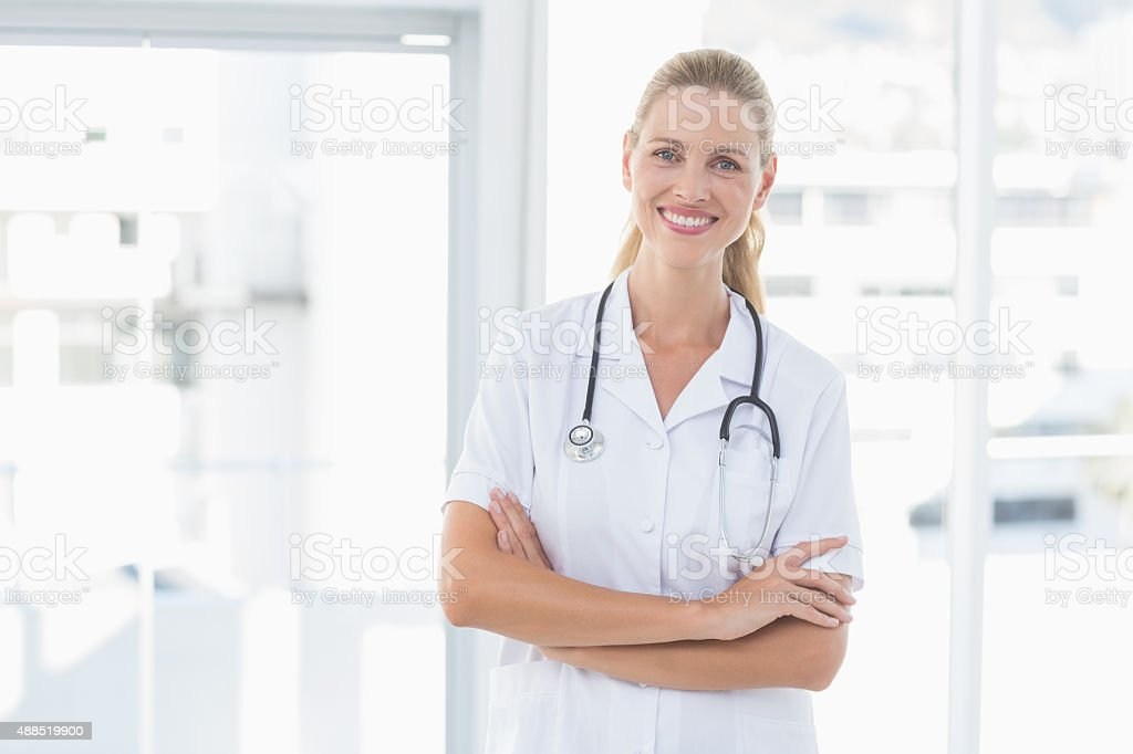 Confident female doctor smiling at camera stock photo