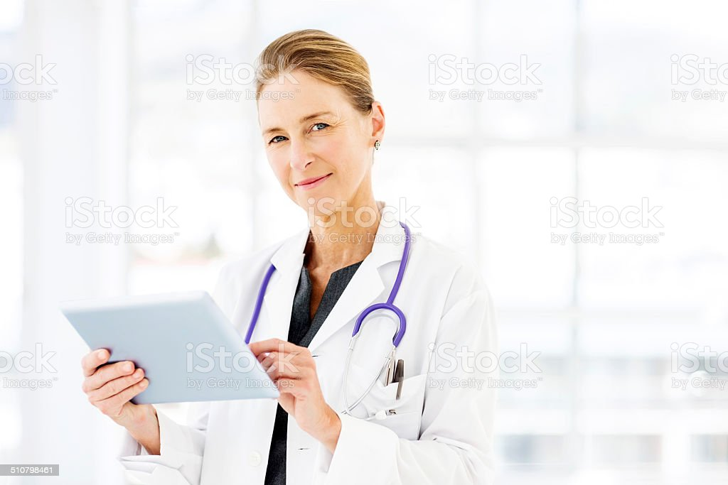Confident Female Doctor Using Tablet Computer stock photo