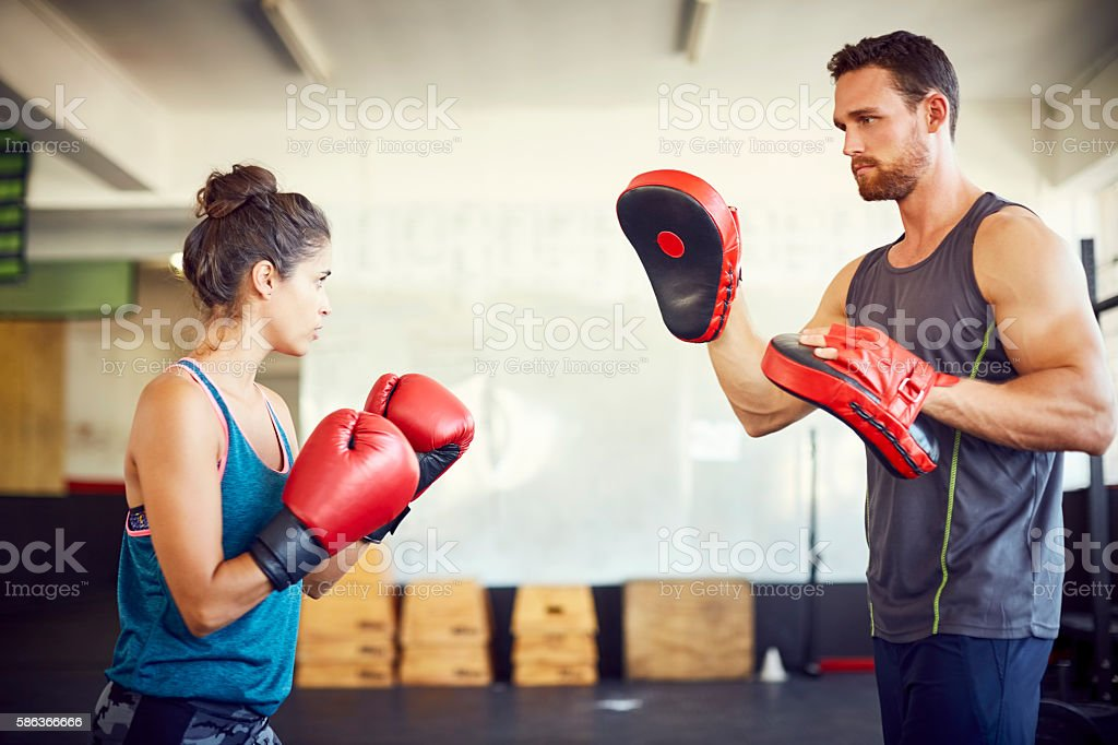 Confident female fit boxer practicing with coach in gym stock photo