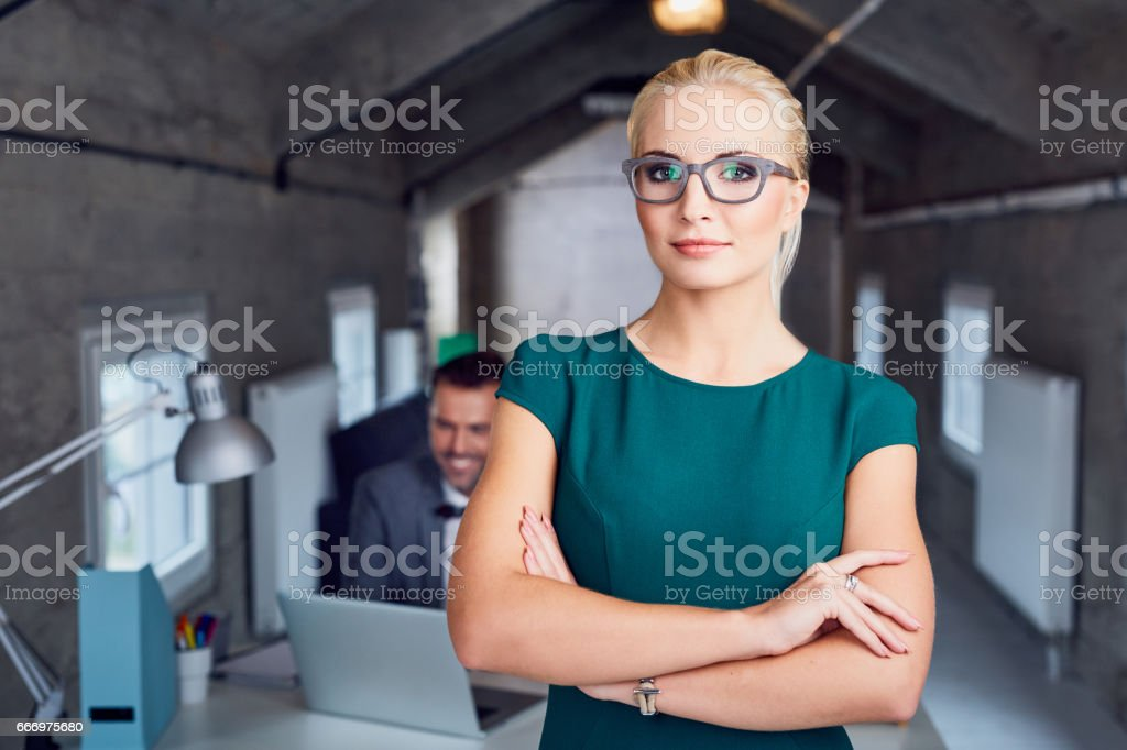 Confident female manager standing in modern office stock photo