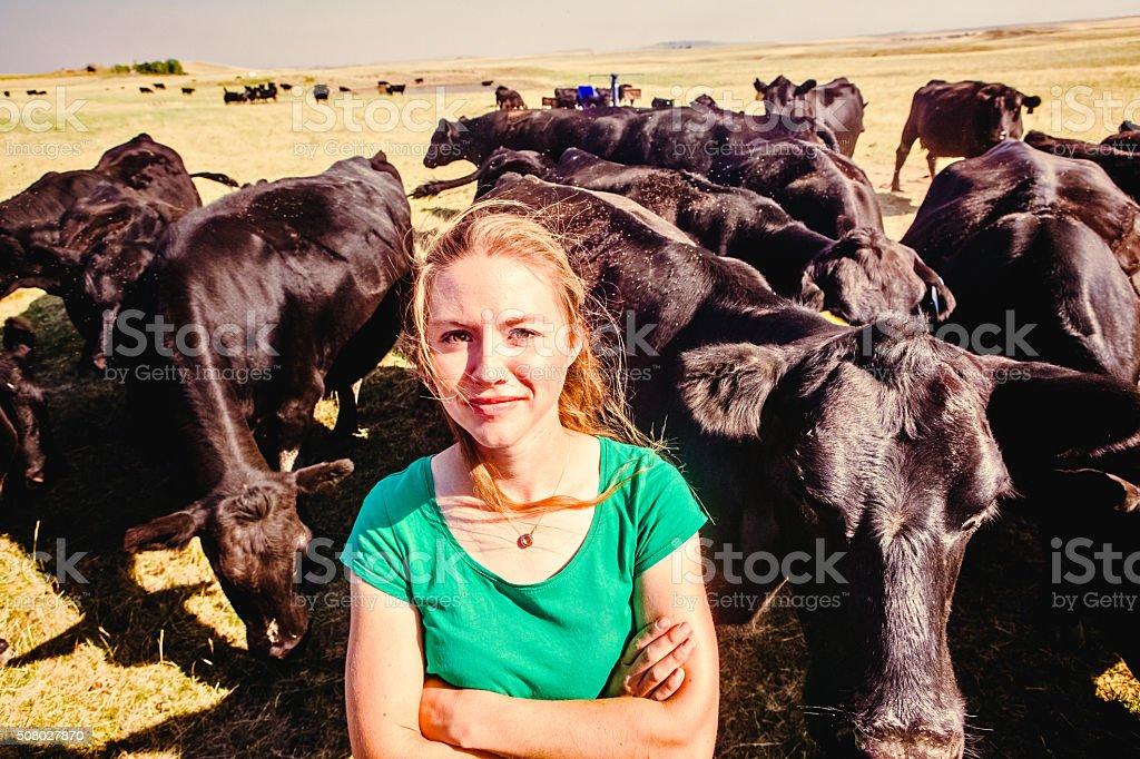 Confident Female Rancher With Herd of Black Angus Cattle stock photo