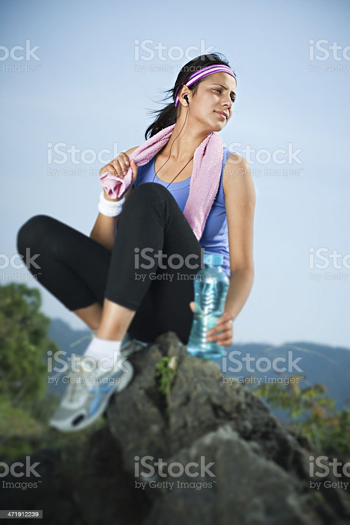 Confident female runner relaxing on a rock and listening music. royalty-free stock photo