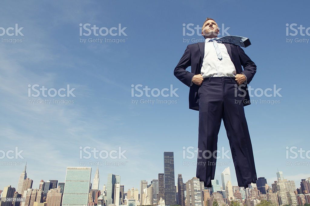 Confident Businessman Towers Over City Skyline stock photo