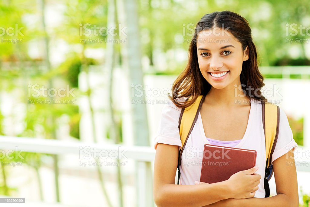 Confident Girl With Book On University Campus stock photo