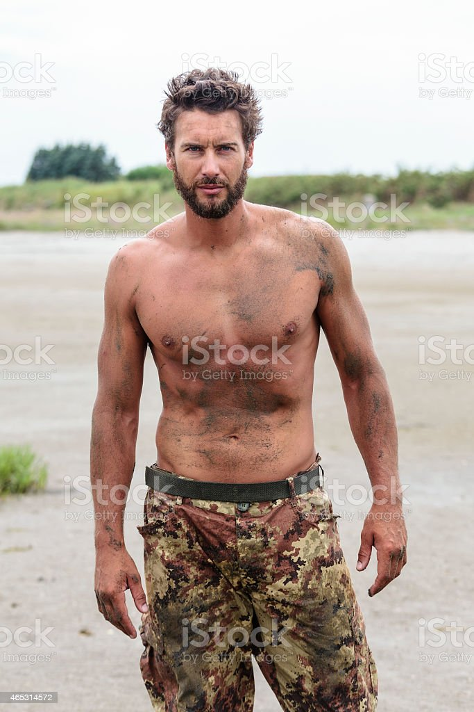 Confident Gorgeous Athletic Army Posing at the Beach stock photo