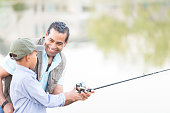 Confident grandfather fishes with grandson