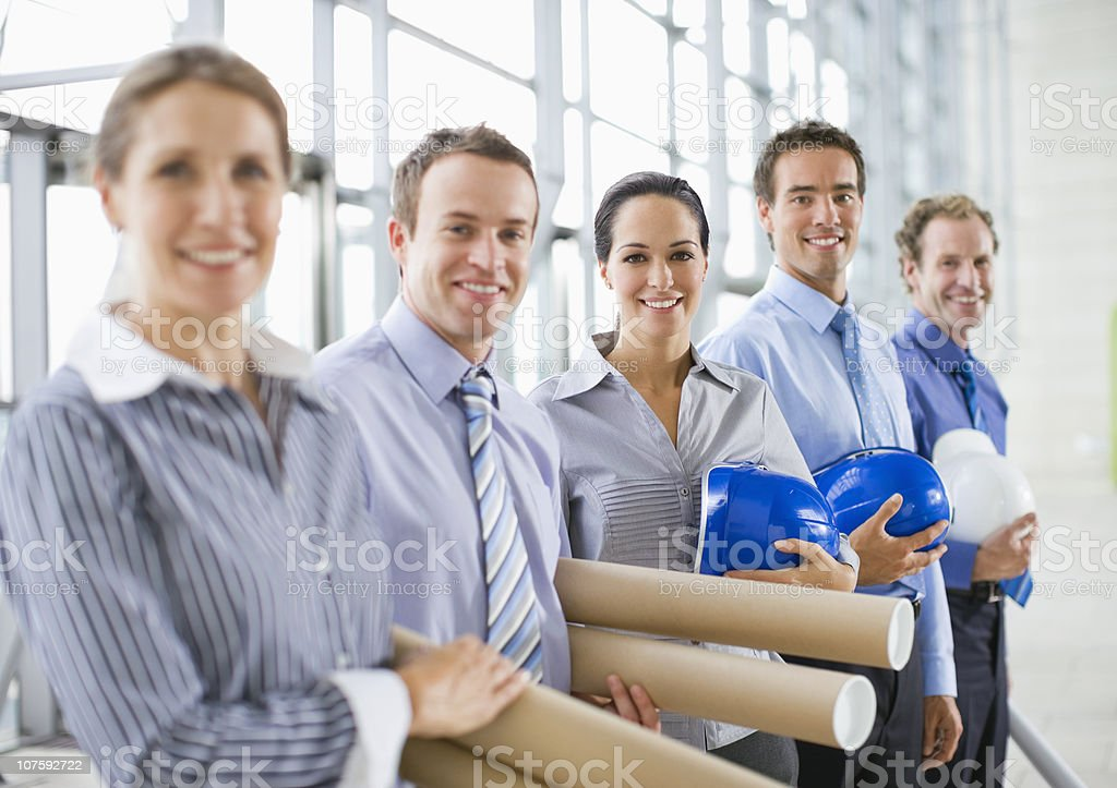 Confident group of architects with hardhats and blueprints in office royalty-free stock photo