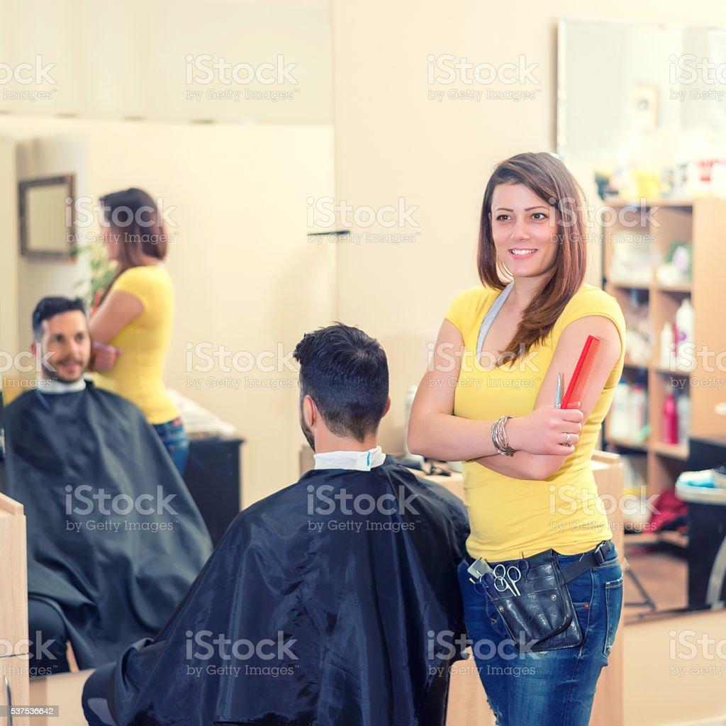 Confident hairdresser in hair salon stock photo