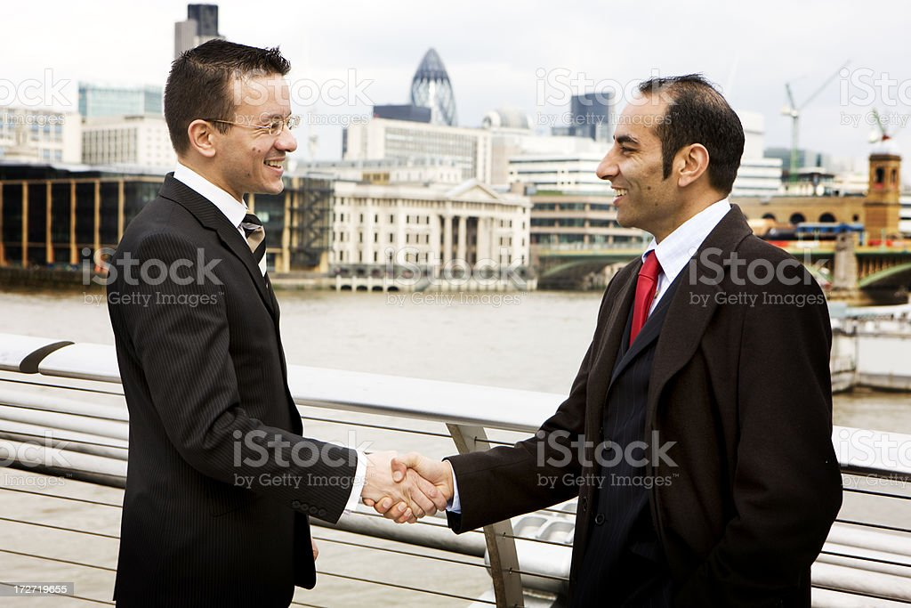 Confident handshake between a diverse pair of London businessmen royalty-free stock photo