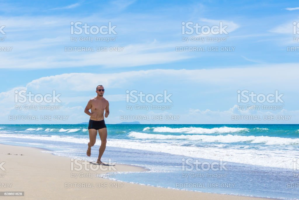 Confident Handsome Man Power Walking Wellbeing Exercise Beach Thailand stock photo