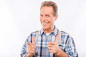 Confident happy aged man in suspenders gesturing fingers straigh