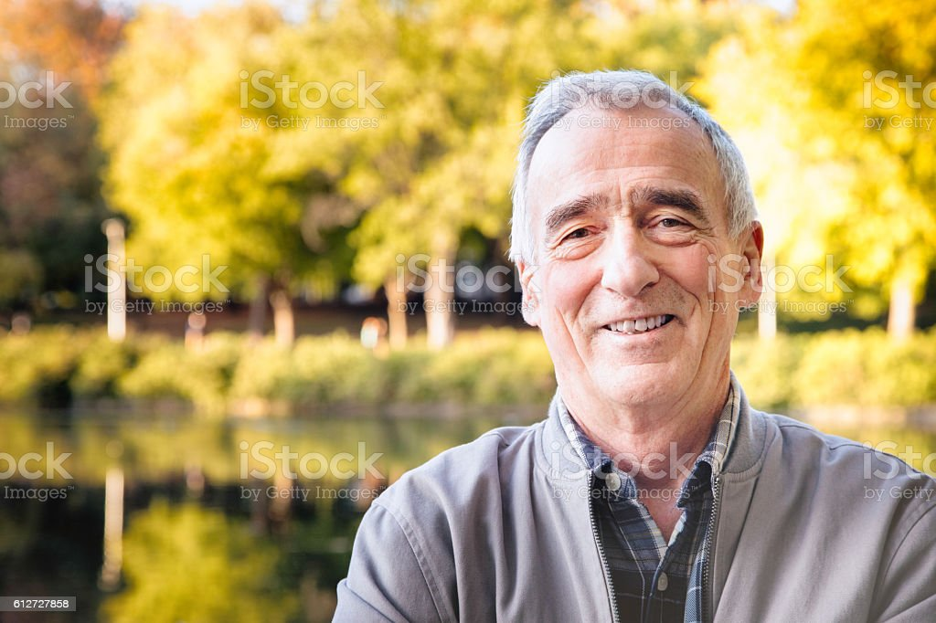 Confident happy senior man Autumn portrait in park stock photo
