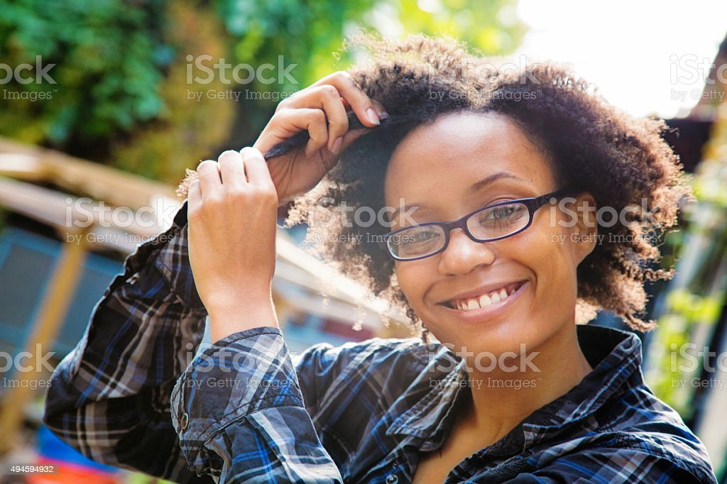 Confident happy young black woman arranging her hair outdoors stock photo