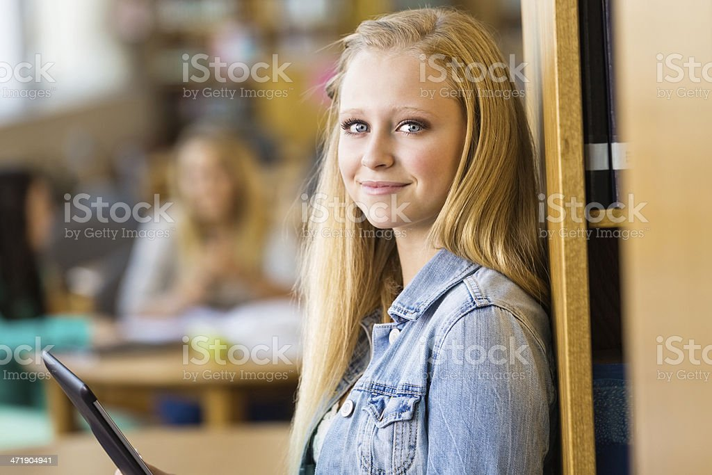 Confident high school student using tablet device to study royalty-free stock photo