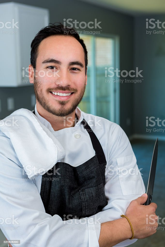 Confident Hispanic chef in kitchen stock photo