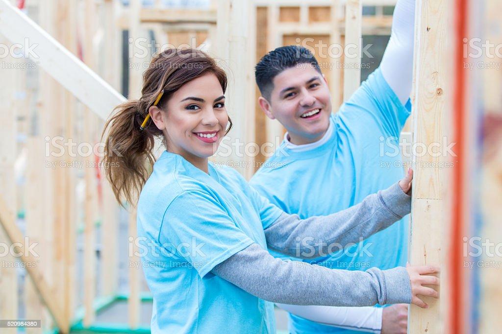 Confident Hispanic couple work on charity home stock photo
