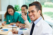 Confident Hispanic doctor smiles during staff meeting