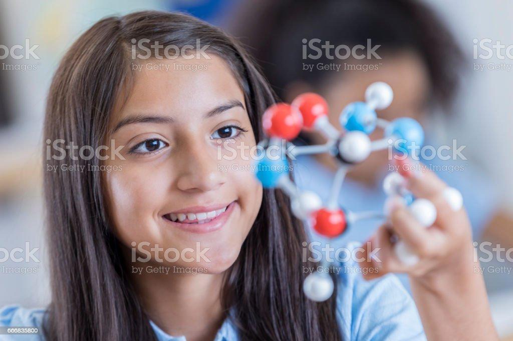 Confident Hispanic junior high student examines molecular structure stock photo