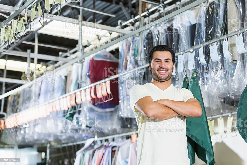 Confident Hispanic man working in dry cleaning store stock photo