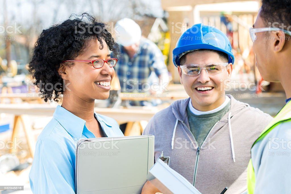 Confident home builder meets with construction crew stock photo