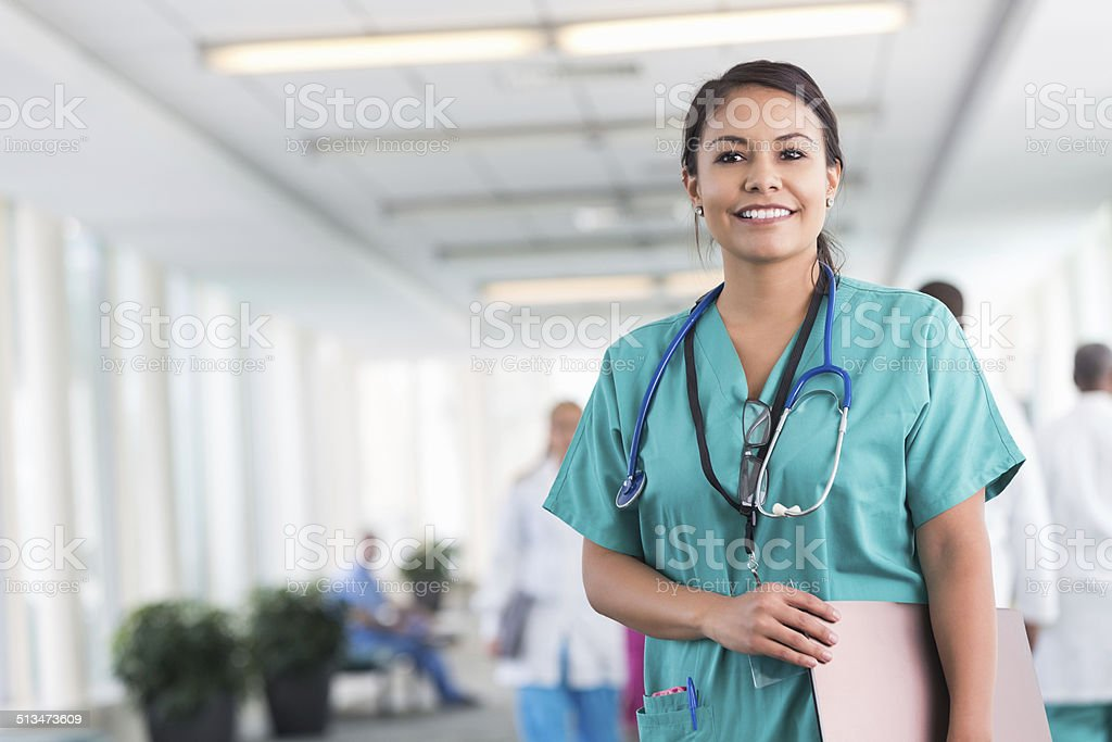 Confident hospital nurse smiling while working in modern hospital stock photo