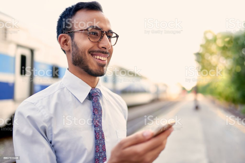 Confident Indian businessman checking his smart phone on a train platform stock photo