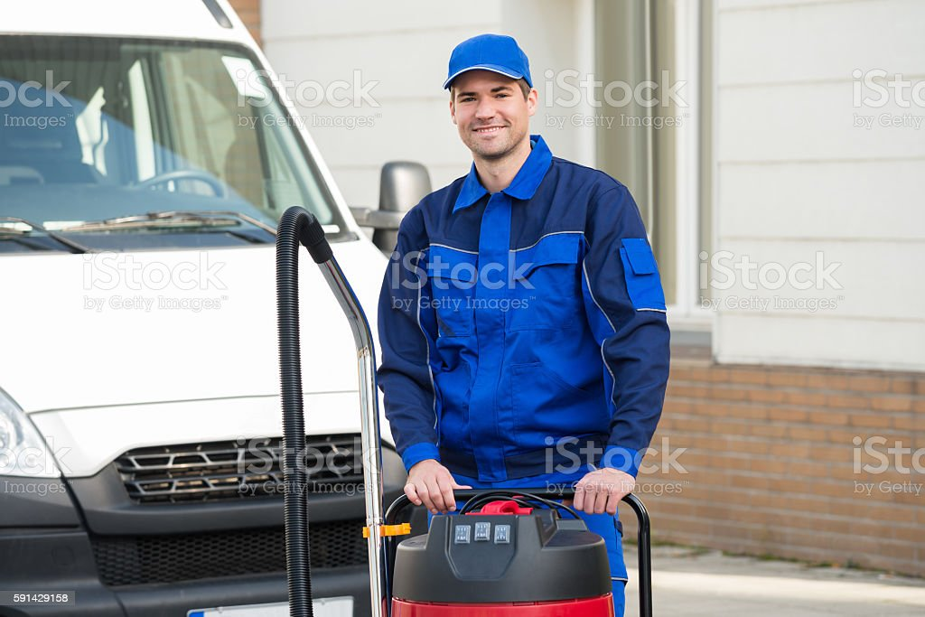 Confident Janitor Standing With Vacuum Cleaner stock photo