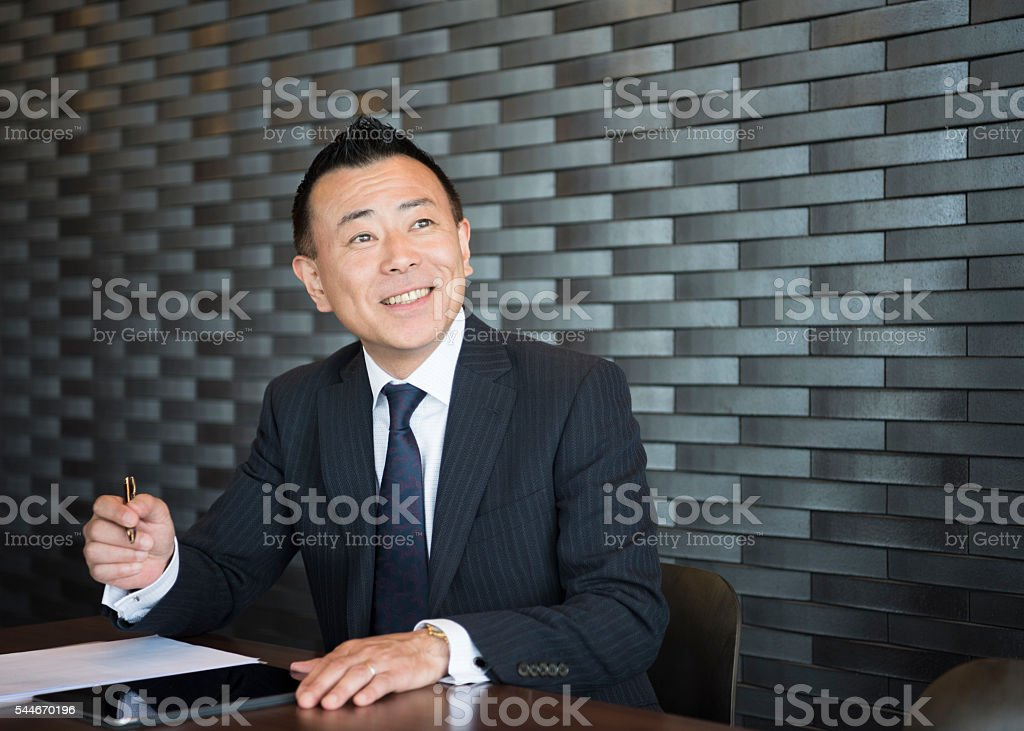 Confident Japanese businessman making notes, smiling stock photo