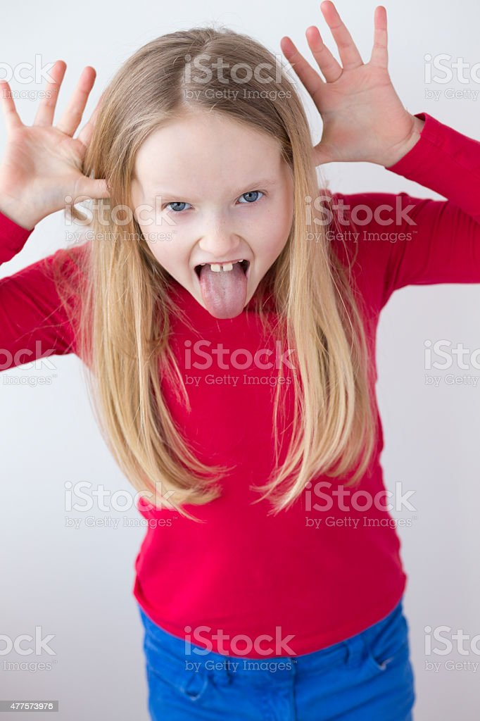 Confident Little Blonde Girl Pulling Faces stock photo
