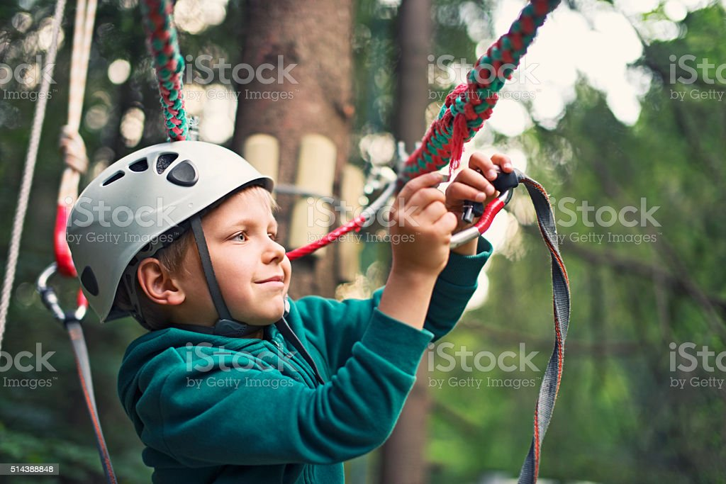 Confident little boy attaching a carabiner to zip line. stock photo