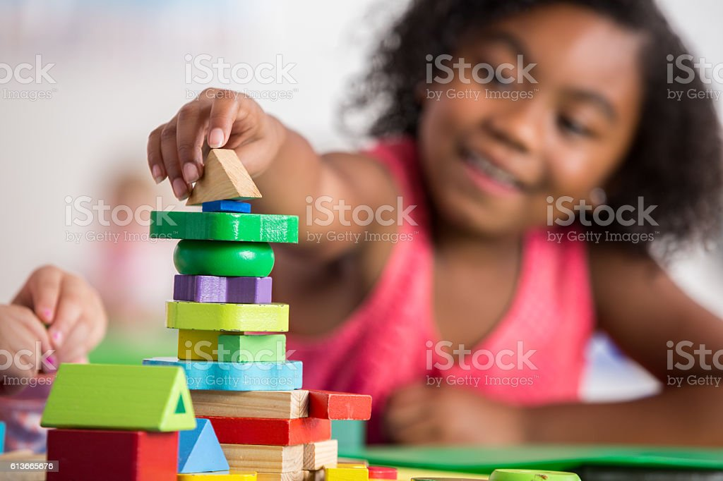 Confident little girl plays with blocks in preschool class stock photo