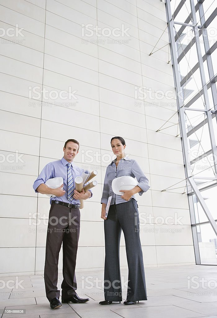 Confident male and female architects with hardhats and rolled blue prints royalty-free stock photo