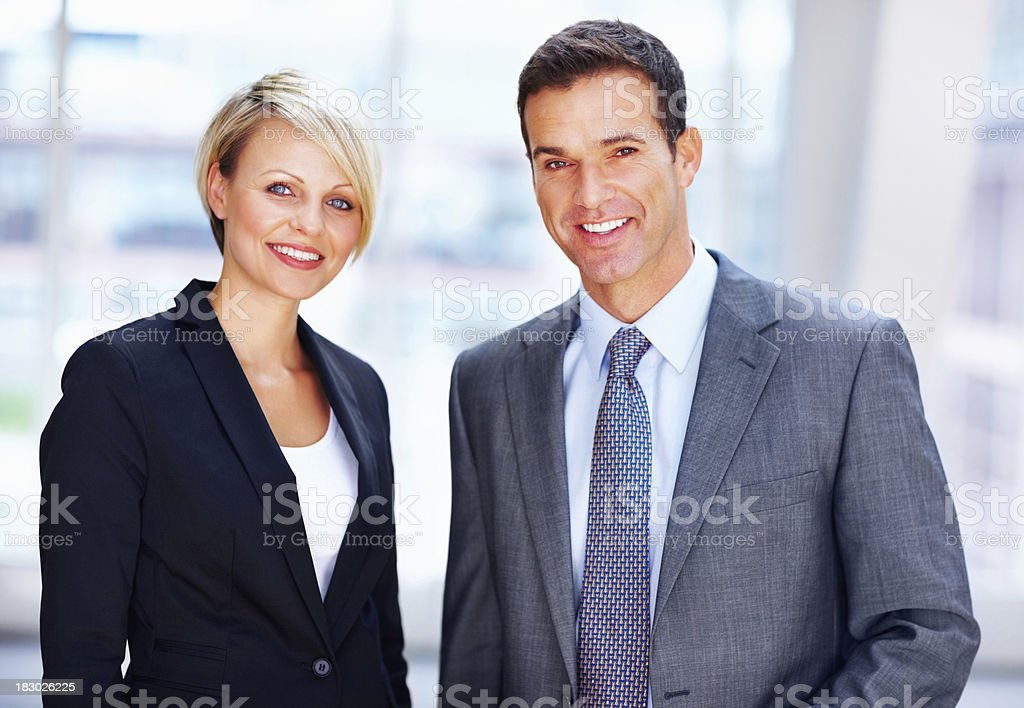 Confident male and female business executives smiling in office royalty-free stock photo