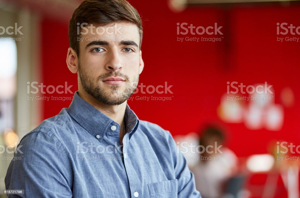 Confident male designer working in red creative office space stock photo