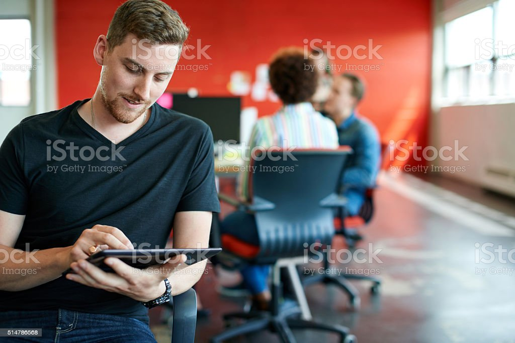 Confident male designer working on a digital tablet in red stock photo