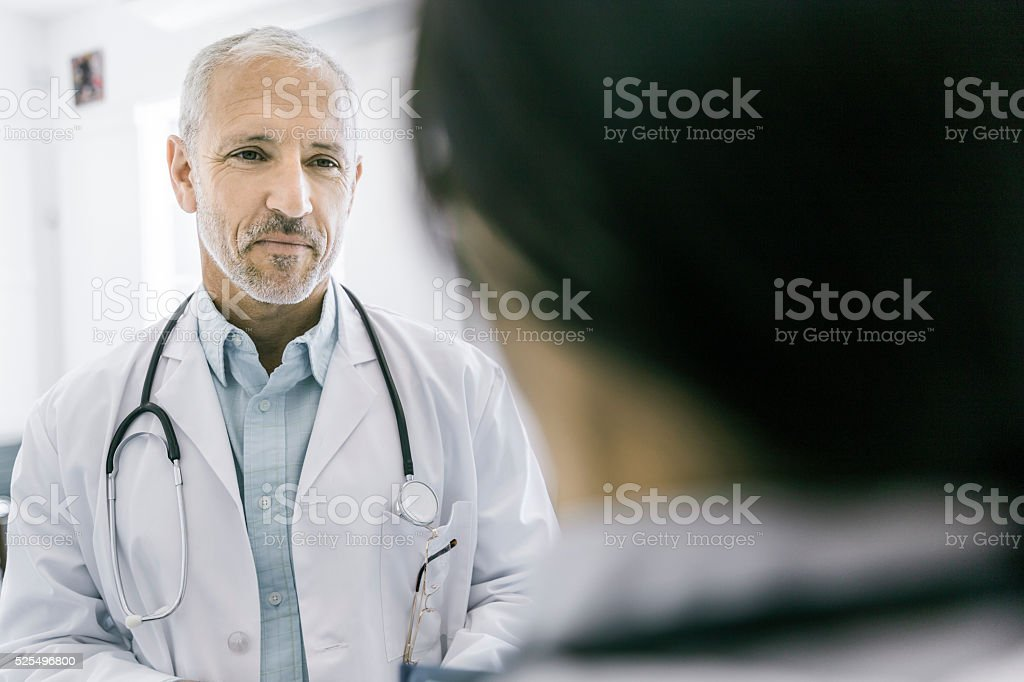 Confident male doctor discussing with colleague stock photo