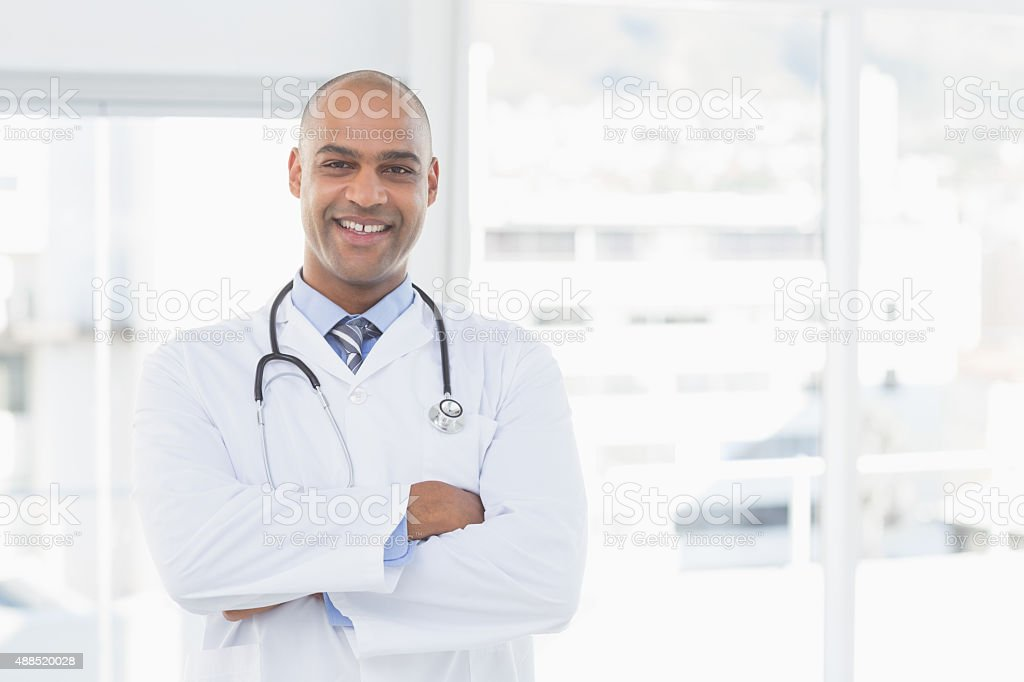 Confident male doctor smiling at camera stock photo