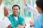 Confident male nurse gives high five during staff meeting