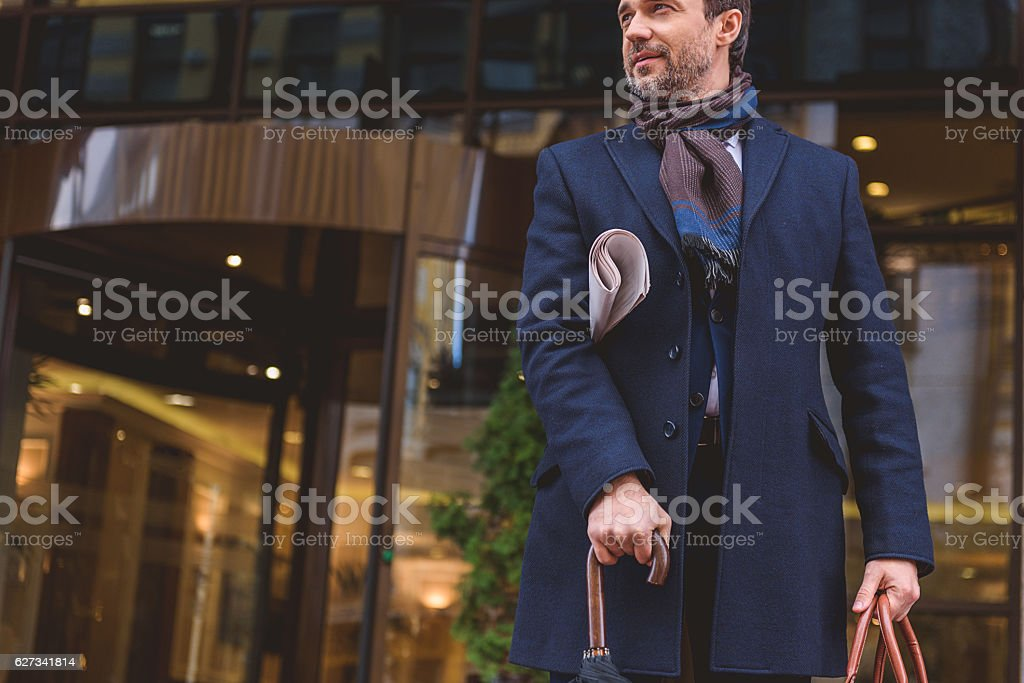 Confident male worker stands near building stock photo